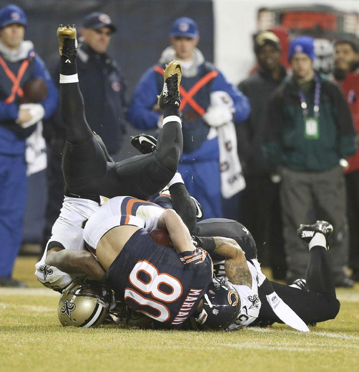 New Orleans Saints defensive back Marcus Ball (36) is upended as he brings down Chicago Bears wide receiver Marc Mariani (80) during the second quarter on Monday, Dec. 15, 2014, at Soldier Field in Chicago.