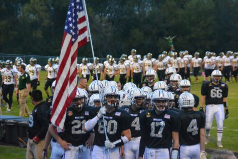 Austen Ferbet leads the Wolves onto to the field on Friday, September 16 at Military Appreciation Night. Prairie Ridge beat Crystal Lake South 56-7.