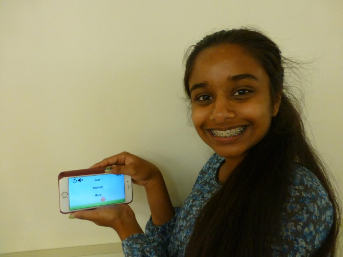 Sophomore Neha Konjeti holds her phone open to the app Bunny Hop she developed the summer before her freshman year of high school.