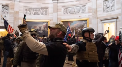 This screenshot from a PBS NewsHour video from inside the Capitol on January 6, 2020 shows a man taking a picture of himself inside the building. Social media photos and videos have since led to arrests.